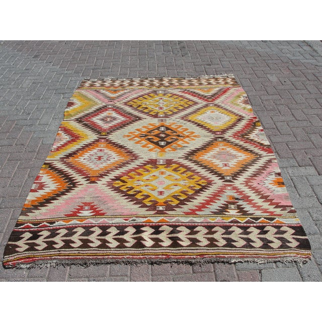 Vintage handwoven Turkish kilim rug. The kilim is nearly 70 years old. It is handmade of very fine quality natural wool in...