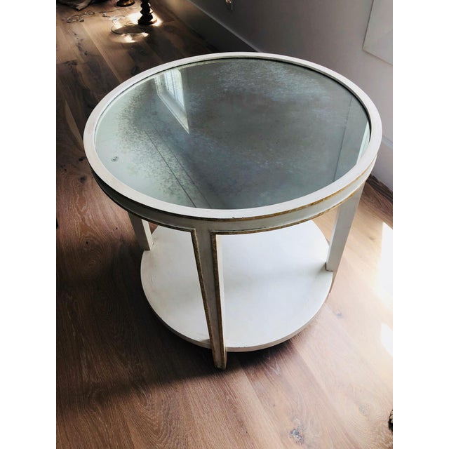 Oly Studio circular Accent Table with a white wood frame, slight gold antique finish on the white wood, and a smoky,...