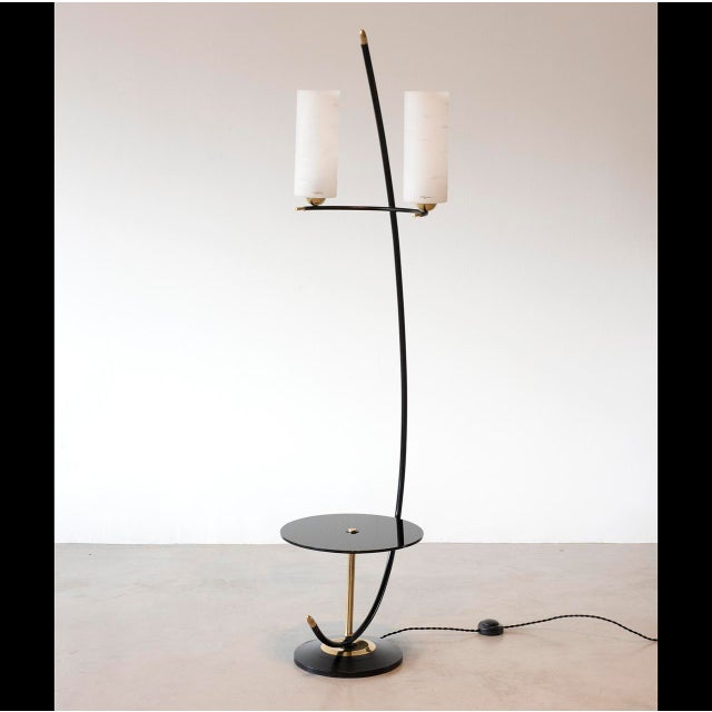 A French floor lamp with black lacquered stem and base, brass accents and a black glass table. The glass diffusers are...