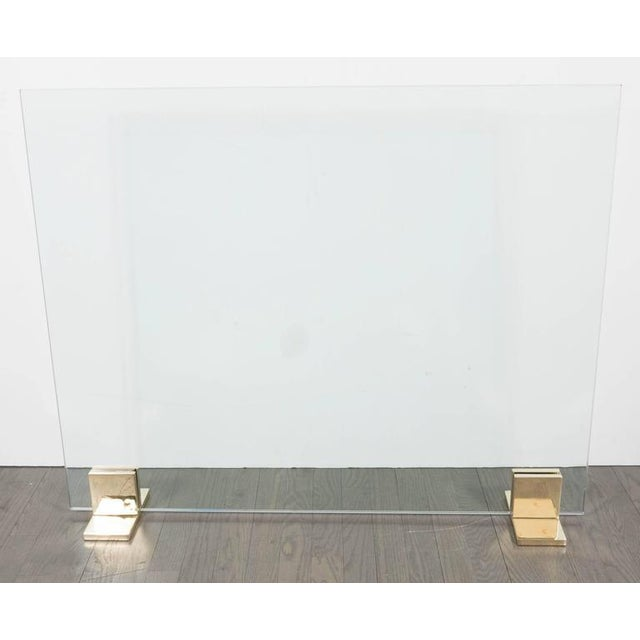 """This custom fire screen features a frameless pane of ½"""" thick tempered glass mounted on a pair of polished nickel feet...."""