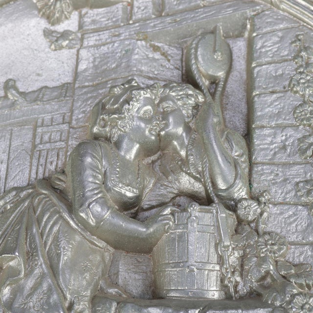 """An antique gilt silver charger features central high relief courting scene """"Am Brunnen"""" (At the Fountain) with pierced..."""
