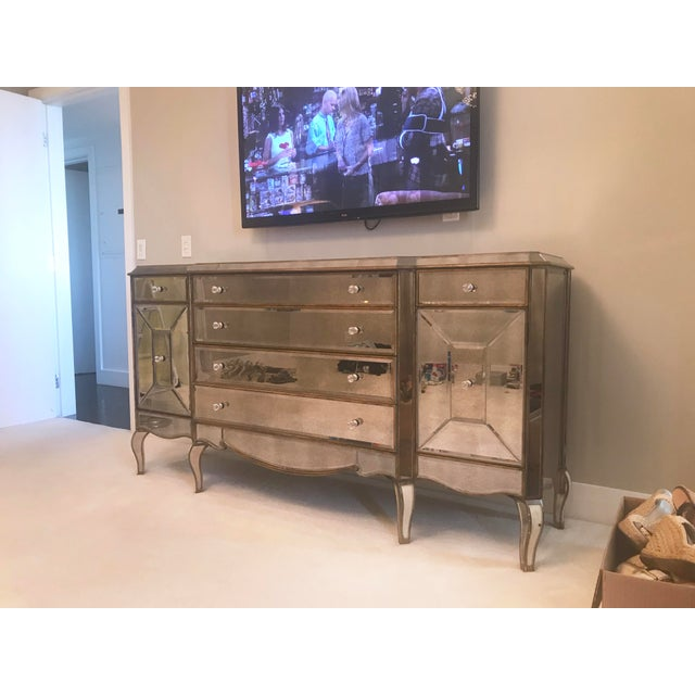 Mirrored dresser with antique mirror panels and gold trim detail. Six drawers and two side cabinets that conceal two...