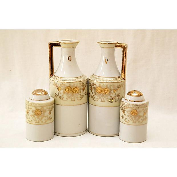 Art Deco oil and vinegar cruets paired with salt and pepper shakers. Embellished with flowers and gilt trim. Maker's mark...