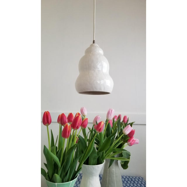Contemporary white ceramic pendant light for kitchen island, bar or nook. Handmade organic form is detailed with thin,...