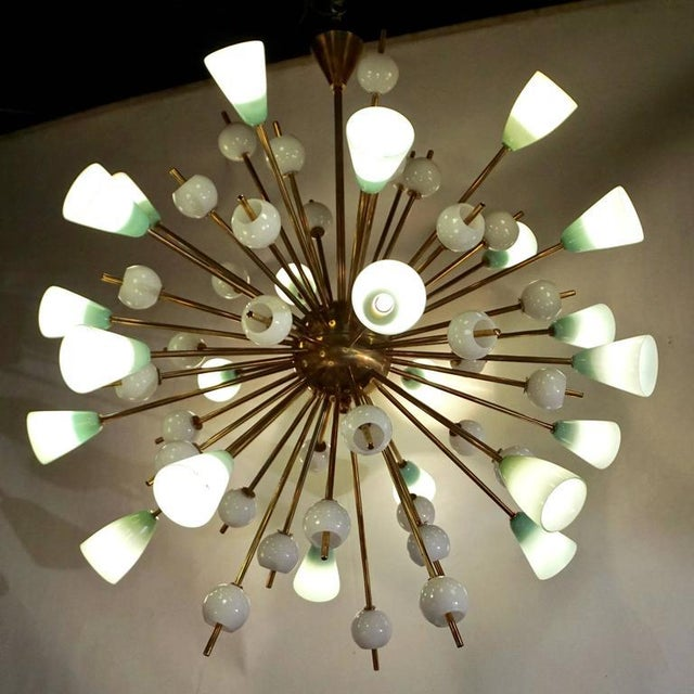 A very elegant Modern Design chandelier with overlaid glass elements, entirely handcrafted in Italy. The brass structure...