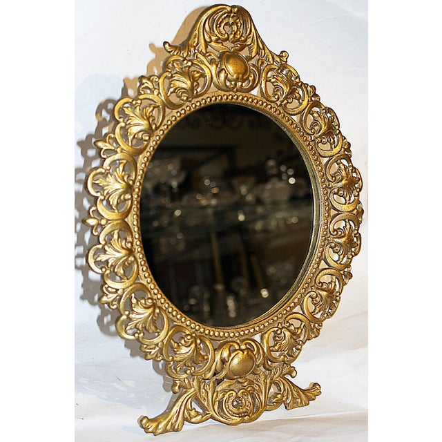 Fit for a princess, a 1940scast and gilt gold metal table top vanity mirror in rococo style, stands on its own rear foot.