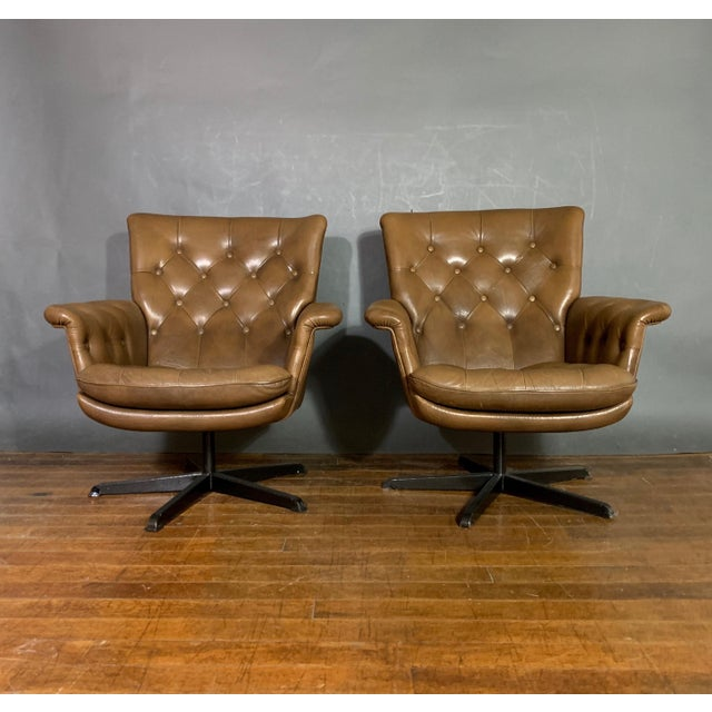 A rare pair of 70s Scandinavian leather swivel chairs with flared arms and deep buttoning overall over five-star metal...