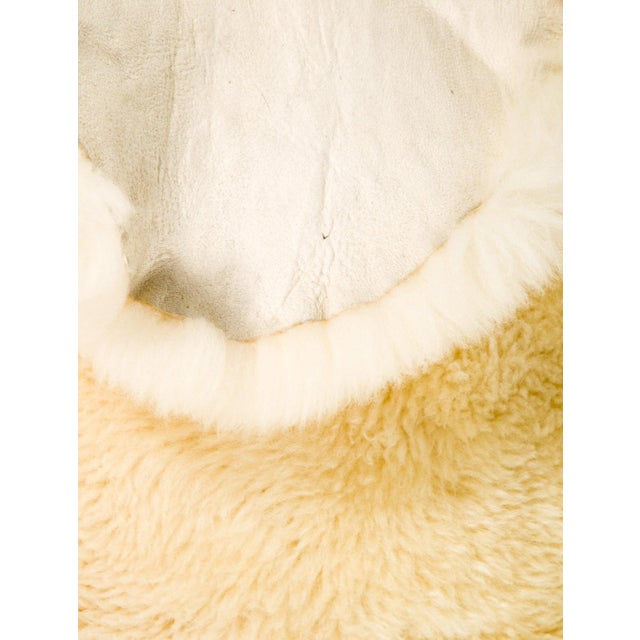 Cozy off-white sheepskin rug or throw. Measures 2′ × 6′1″