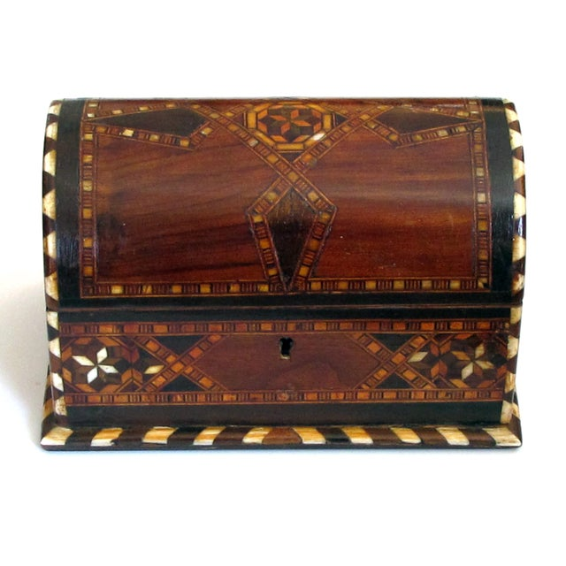 The domed rectangular box above a conforming body; the whole with fine geometric inlay of exotic woods and bone