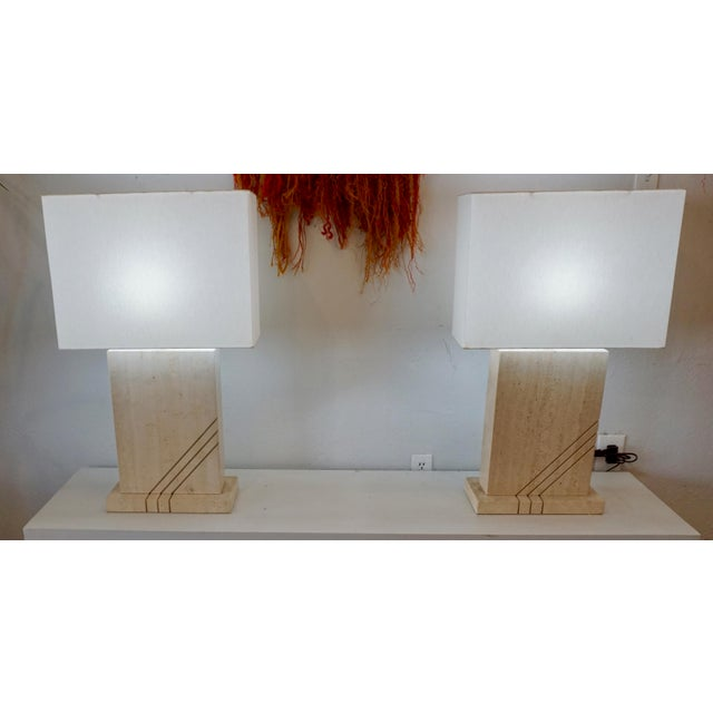 Solid,striking travertine table lamps with white linen shades.