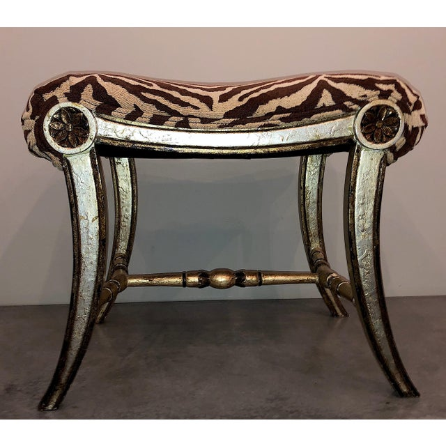 Pair of Hollywood Regency silver gilt zebra upholstered benches. Each feature splayed legs, rosettes, swag seat, and...