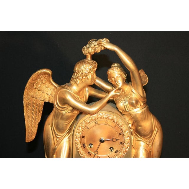 Very fine gilt bronze figural mantel clock featuring cupid (also known as amour) swooning a butterfly winged psyche. This...