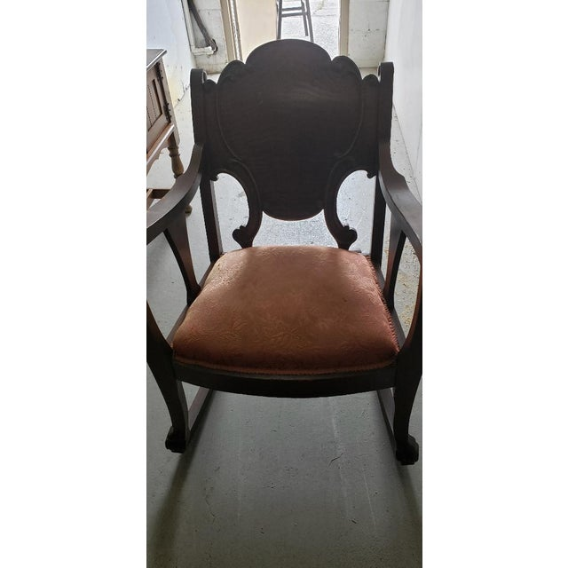 1950 Solid Wood Antique Vintage Rocking Chair. Beautiful Ornate Rocking Chair with a design on the back of the seating....