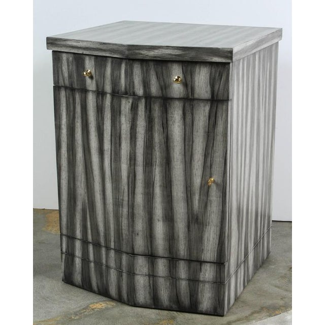 Paul Marra Pinnacle Nightstand shown in grey zebra finish with one drawer and one door. Removable shelf. There is a pair...