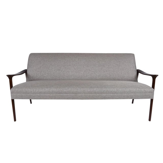This 1960's Vintage Danish Mid-Century Modern-style sofa features a teak wood frame that has been stained in rich, dark...