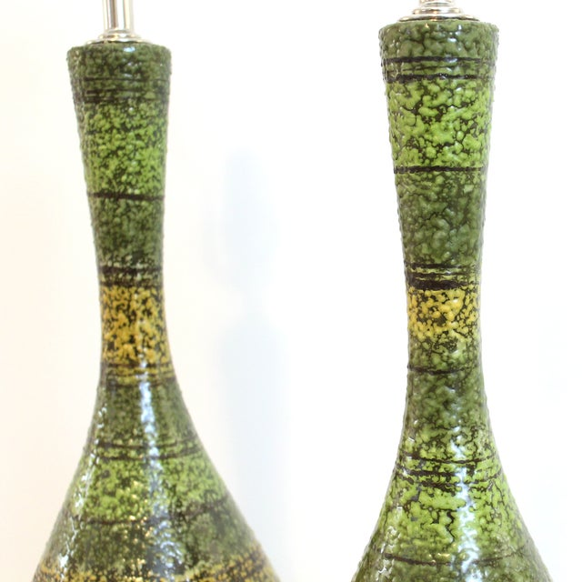 A pair of refurbished vintage 1960s pottery table lamps featuring a hand decorated glaze in vibrant tones of lime,...