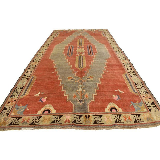 Charming and unique, this hand knotted wool antique Caucasian Tribal rug features a sweeping geometric pattern across a...
