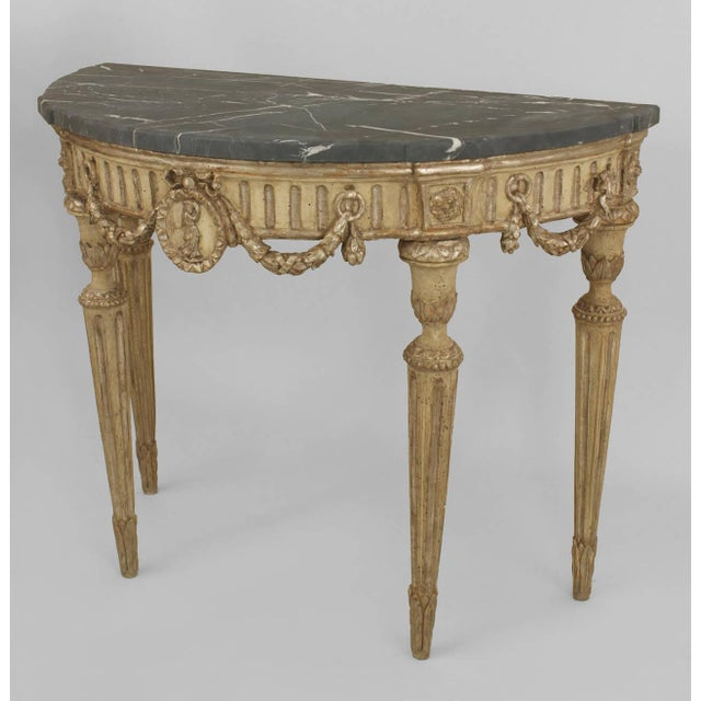 Pair of Italian neoclassic demilune silver-gilt and grey painted console tables with a fluted apron having a central...