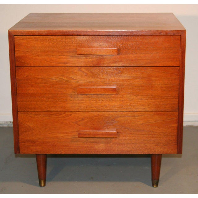 Pair of walnut three drawer nightstands on tapered legs with brass sabot. Beautiful grain to veneer. Wood handles.