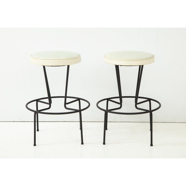 Pair of wrought iron stools with vintage white vinyl seats. Designed and produced by Frederick Weinberg, c. 1950's. Price...