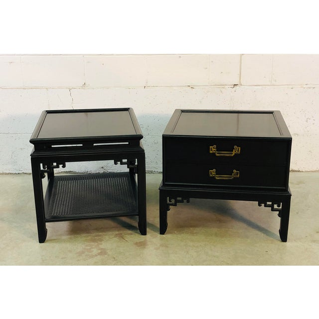 Vintage pair of Hekman Furniture Co black lacquered Asian Modern side tables. One table has two drawers for storage with...