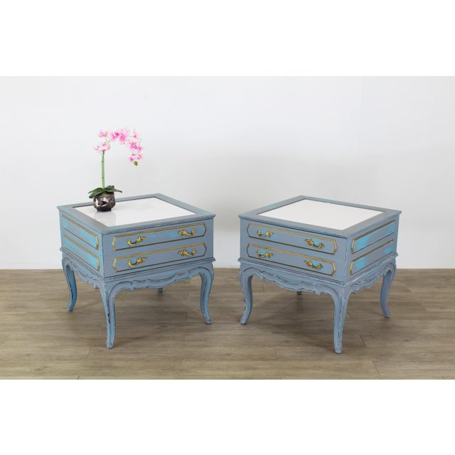 Pair of mid-century French style nightstands with white acrylic tops, single drawer and gold painted handles This pair of...