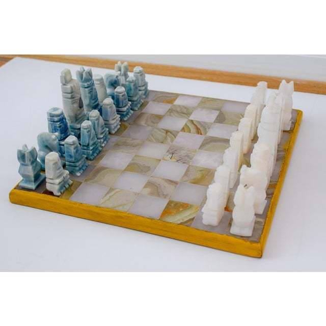 Gorgeous hand carved onyx blue and white chess pieces adorn this white and tan chess board. All of the pieces are carved...
