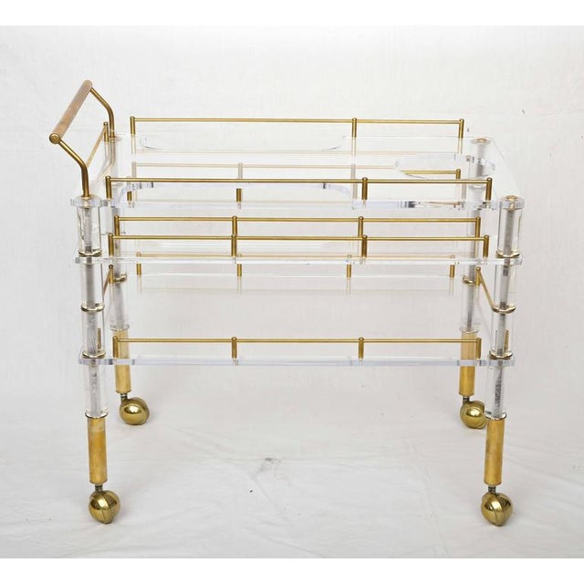 Offered is a beautiful crafted Lucite and brass bar cart on casters in the style of Charles Hollis Jones. It has two...