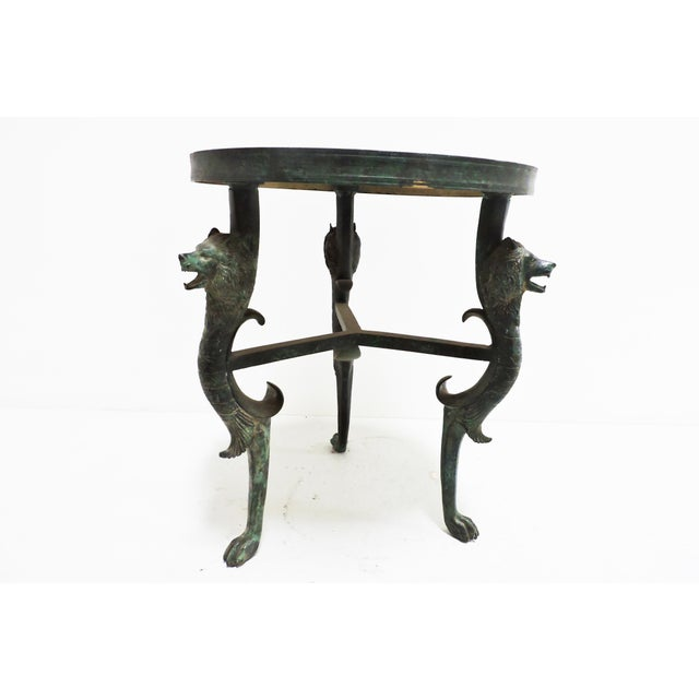 A Luciano Tempo creation, this bronze short three-legged table is akin to its taller version, featuring toothy wolves as...