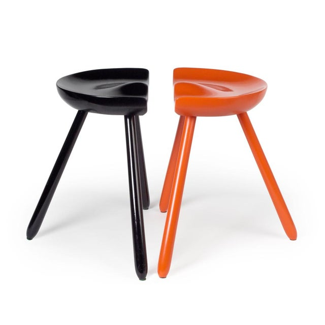 Milking stools with sculpted seats supported on three legs; one in orange and one in black lacquer. After a design by...