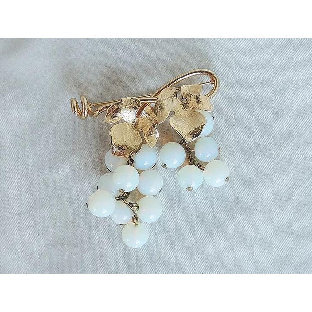 """1950s goldtone leaves with white opalescent glass grape clusters brooch with security clasp. Marked """"Napier."""" Measures:..."""