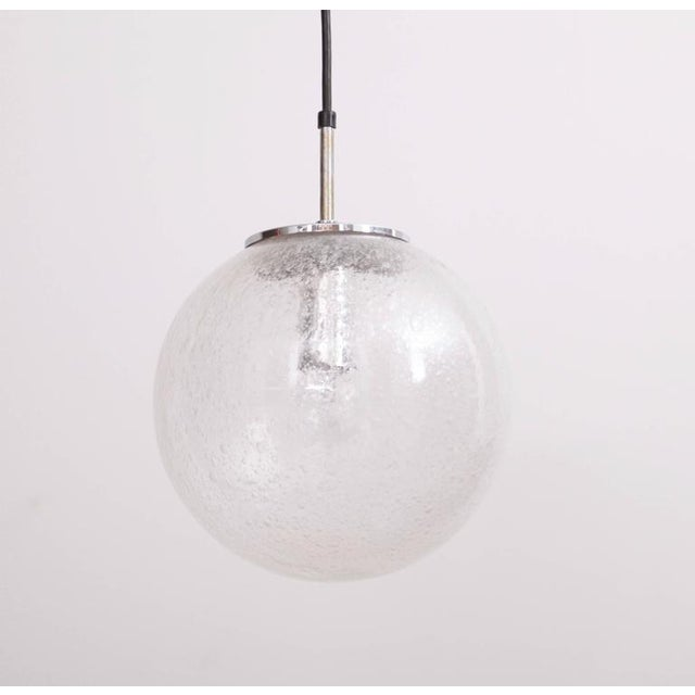 Globe pendant lamps made of handblown glass and chrome hardware. They were produced in the 1970s by the German high end...