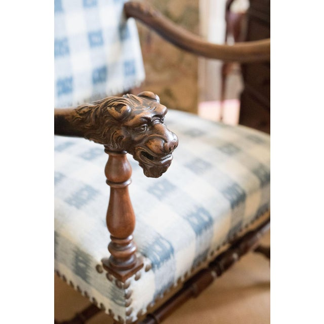 Large impressive walnut open armchair with carved arms terminating in fierce animal heads, carved legs and an H-stretcher,...