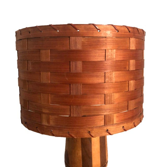 Mid-century vintage solid wood table lamp. The base is a beautiful inlaid wood column and the lampshade is basket weave.