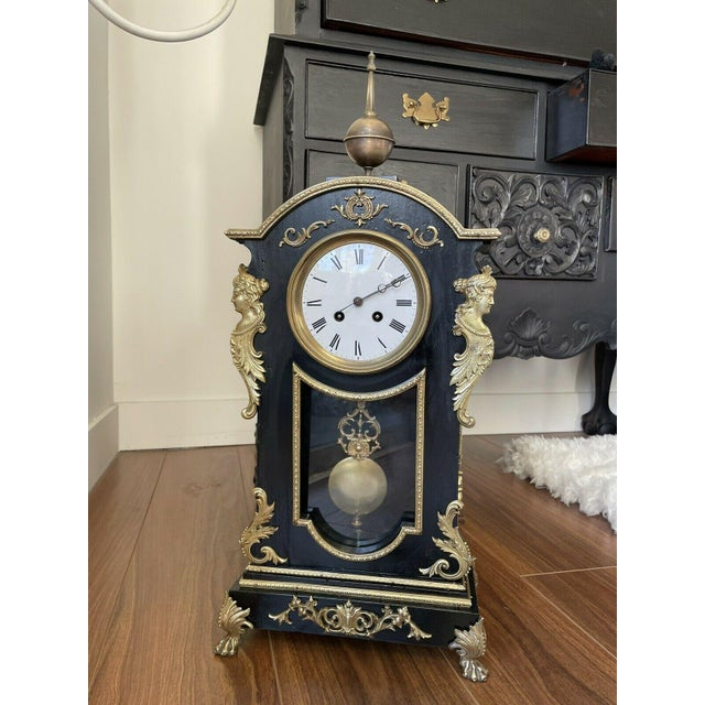 For sale is an antique French clock. The clock features an ebonized wooden case with bronze ornaments throughout. We were...
