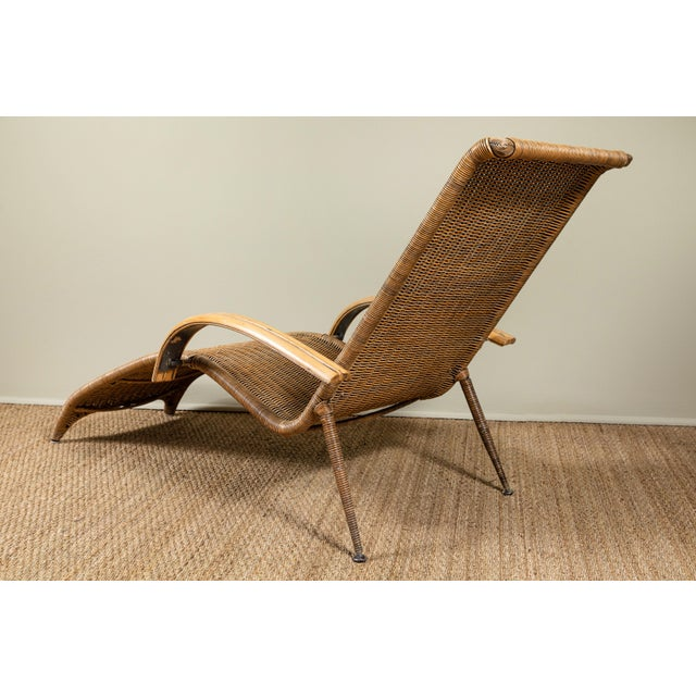 Rattan lounge chair. Bamboo arms and caning over legs.