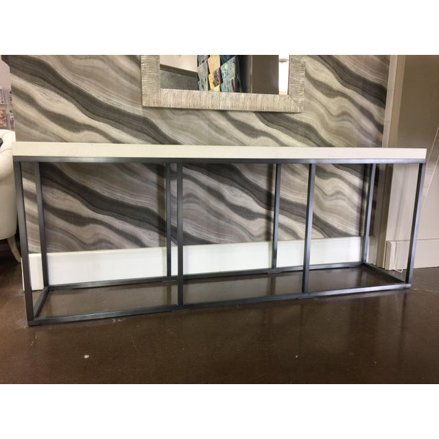 "This is an axel console table that features a brushed ebonized iron frame and a 2"" boxed limestone top. It is a Troy floor..."