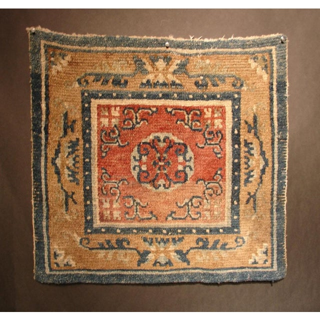 A mid 19th century Tibetan hand woven, natural dye, wool, square meditation carpet featuring a central medallion on a red...