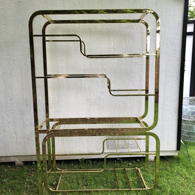 This beautiful vintage bent brass and glass shelving unit is an amazing addition to any MCM collection. Designed by Milo...
