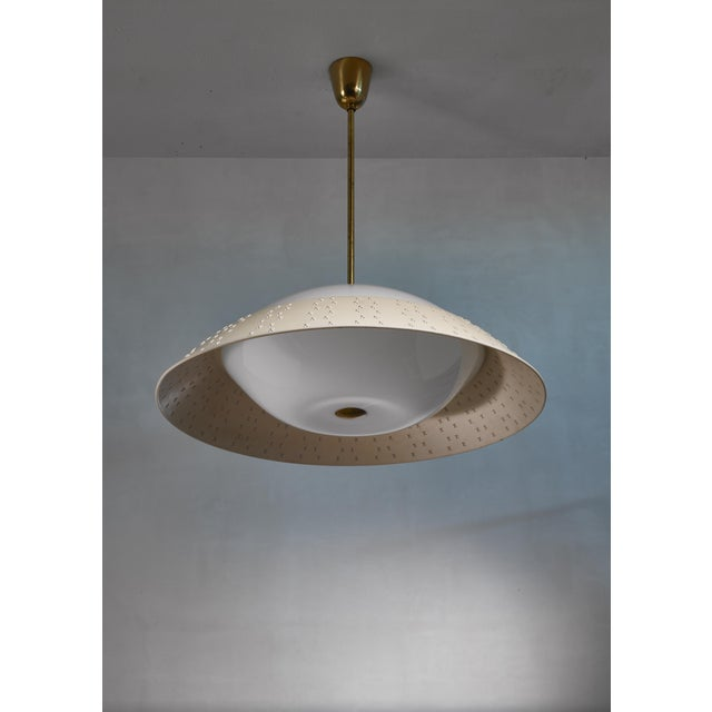 A model 1102 Lisa Johansson-Pape pendant lamp for Orno. The lamp has a large (72 cm diameter) shade hanging from a brass...