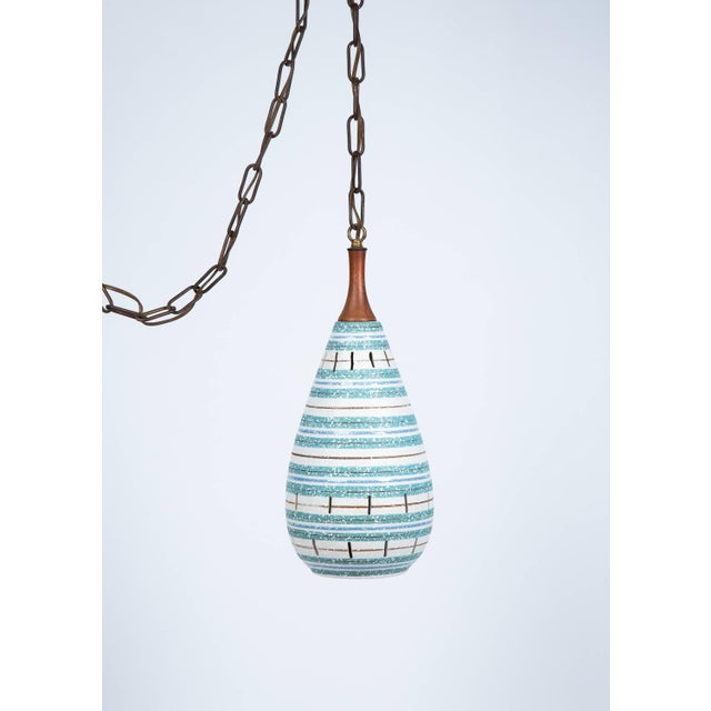 Italian turquoise and white stripe ceramic hanging pendant chandelier has textured glaze and walnut stem. Light...