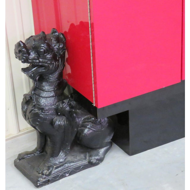 Red lacquered cabinet. Bar interior with glass shelves. Ceramic foo dogs.