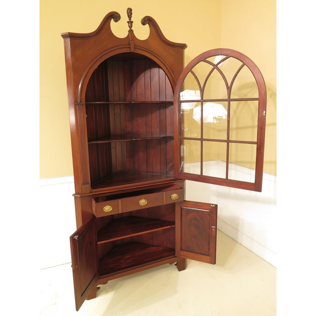 John Bair custom made mahogany corner china cabinet. Features dovetailed drawer construction, pediment top with finial,...