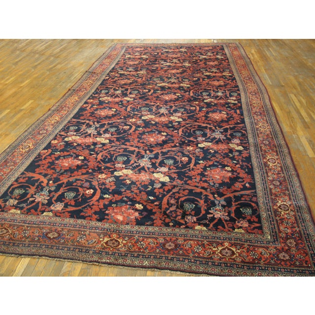 Antique Bijar Persian Rug with a navy background and red border.