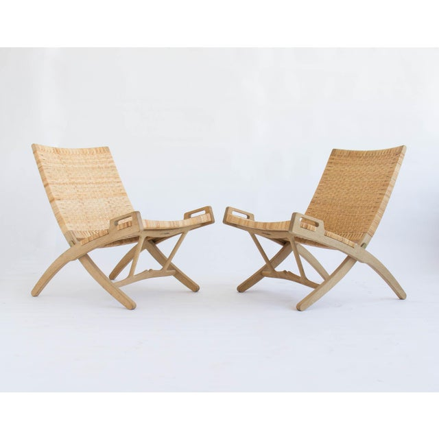 Pair of folding lounge chairs in oak and cane, made by PP Møbler in 2007. The pair was designed by Hans Wegner in 1949....