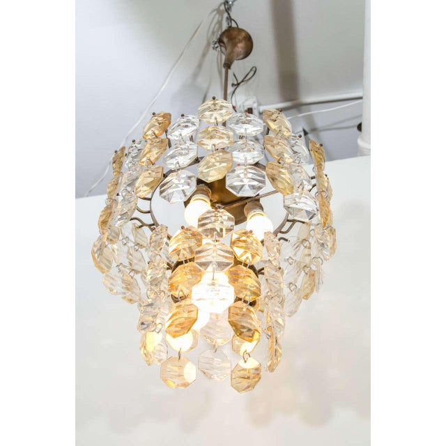 A vintage two-tiered chandelier, composed of faceted gold-toned and clear Murano glass discs.