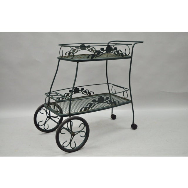 Item: Meadowcraft Dogwood Green Wrought Iron Tea Cart Details: Wrought iron construction, Rubber and plastic wheels, Two...