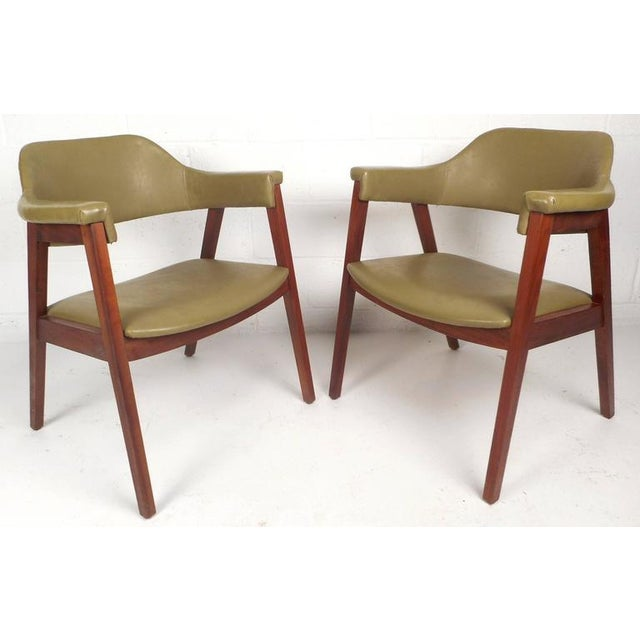 Stunning pair of vintage modern chairs with green vinyl upholstery covering the seat and backrest. The beautiful walnut...