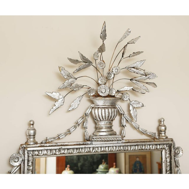 Large pair of silver leafed Italianate mirrors. The top of each mirror has an urn with an arrangement of stemmed leaves....