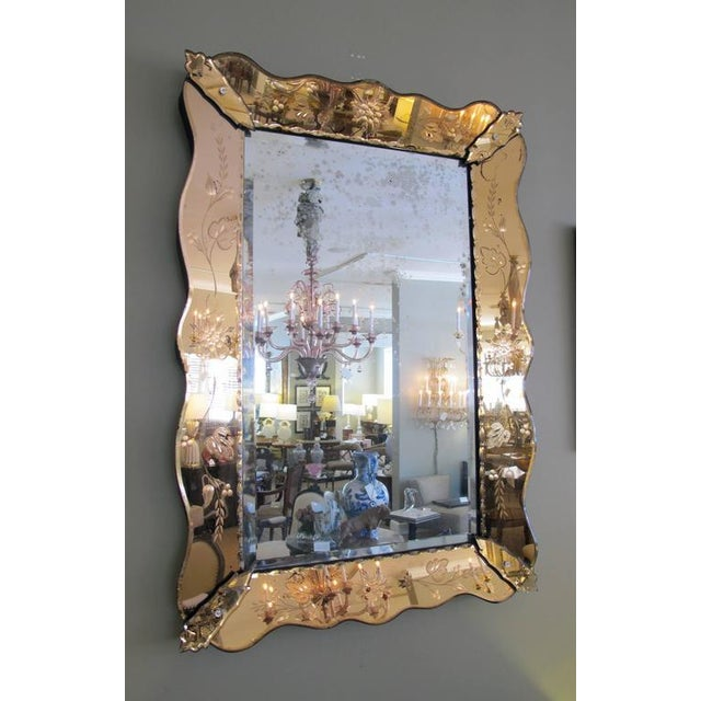A shapely Italian 1930s mirror with etched peach-colored surround; the original rectangular beveled plate within a peach...